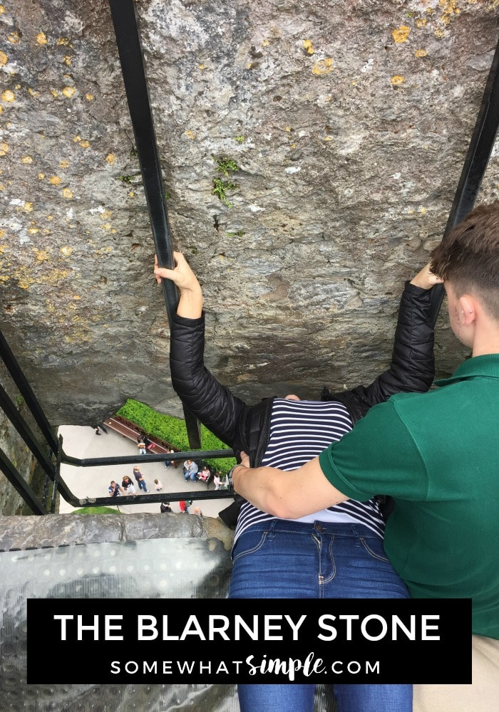 a woman laying on her back and holding on to two metal bars while she kisses the Blarney Stone at the top of the Blarney Castle in southern Ireland