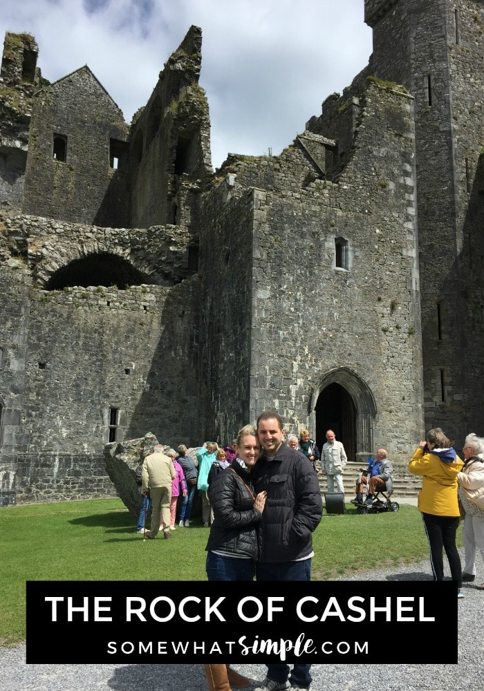 an attractive couple standing in from of the rock of cashel chapel in southern ireland