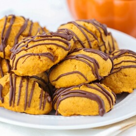 a plate full of chocolate glazed pumpkin cookies