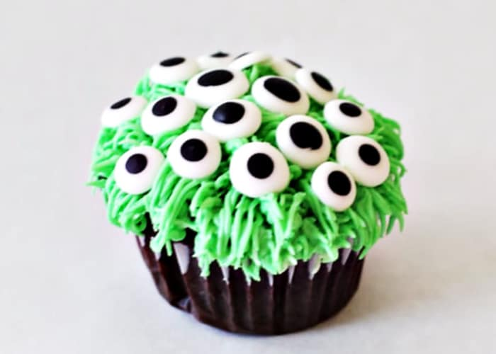 a cupcake topped with stringy green frosting and candy monster eyeballs