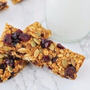 two homemade pumpkin granola bars laying on a counter top next to a glass of milk