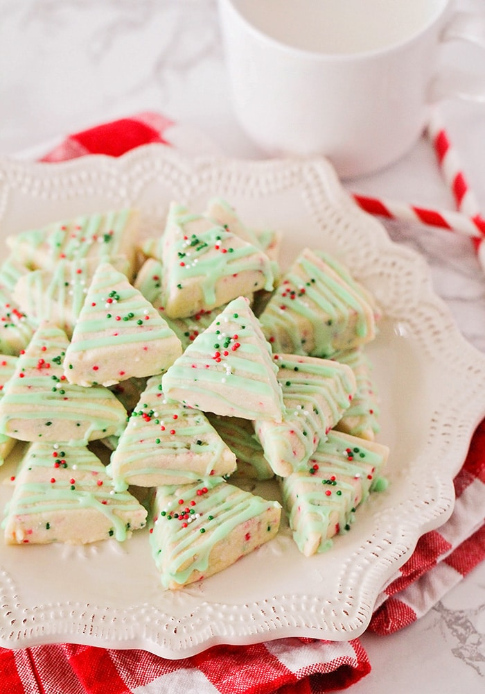 A pile of Christmas Shortbread Cookies on a white plate with red and white straws laid next to the plate.