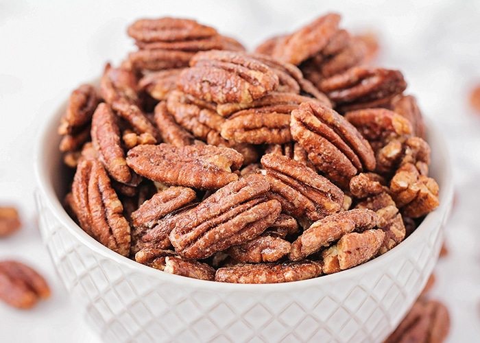 a bowl of Candied Pecans in a white bowl are a delicious super bowl treat idea