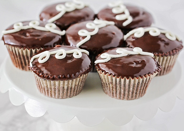 a white cupcake stand full of Homemade Hostess Cupcakes made using this recipe with chocolate icing and a swirl of the cream filling on top