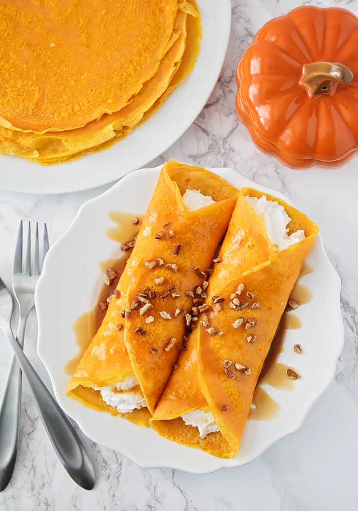 looking down on a pair of savory homemade Pumpkin Crepes with a creamy filling and a stack of cooked crepes behind them