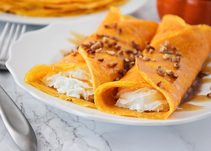 2 pumpkin crepes on a plate filled with a cheesecake filling and topped with pecans and a caramel sauce