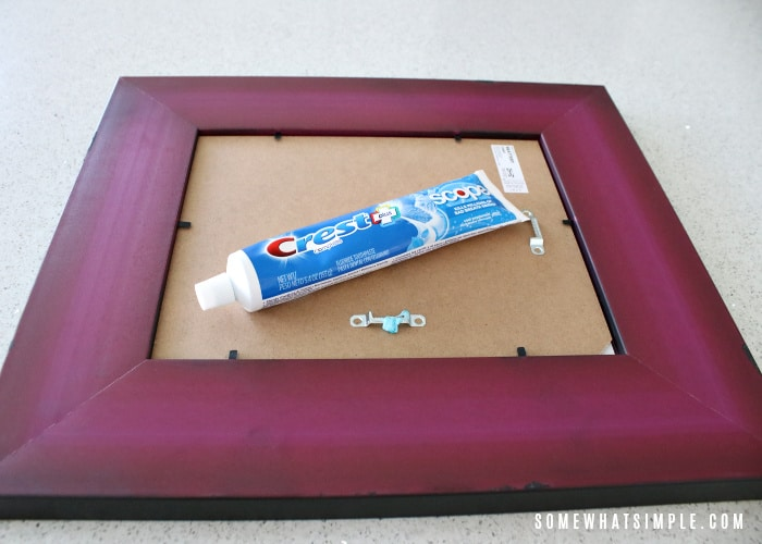 a tube of toothpaste laying on the back of a picture frame