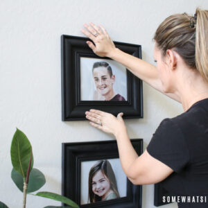 a beautiful woman hanging a picture on a wall