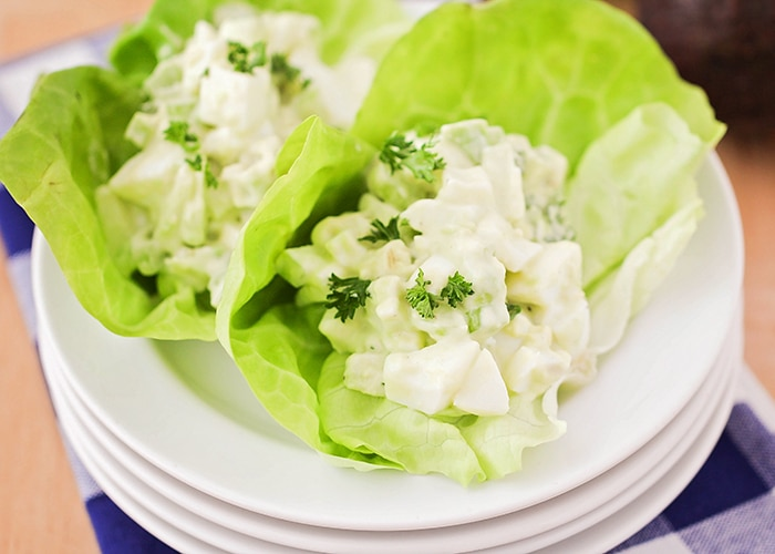 looking down on a stack of white plates with two large leaves of lettuce on top with each filled with a serving of Avocado Egg Salad