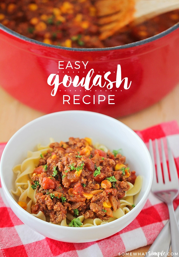 a white bowl filled with american goulash in front of a red pot filled with more goulash and the words easy goulash recipe overlayed in the middle of the image