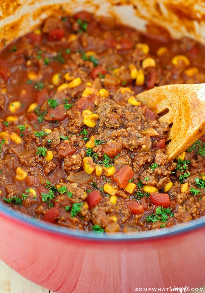 a red pot full of this easy Goulash recipe with a wooden spoon stirring the ground beef, corn, tomatoes and other ingredients