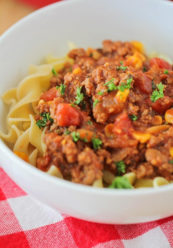 a close up of a white bowl filled with american goulash which is made up of pasta and topped with goulash