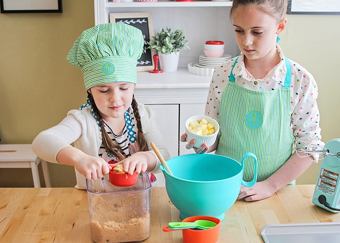 two young girls making cookies