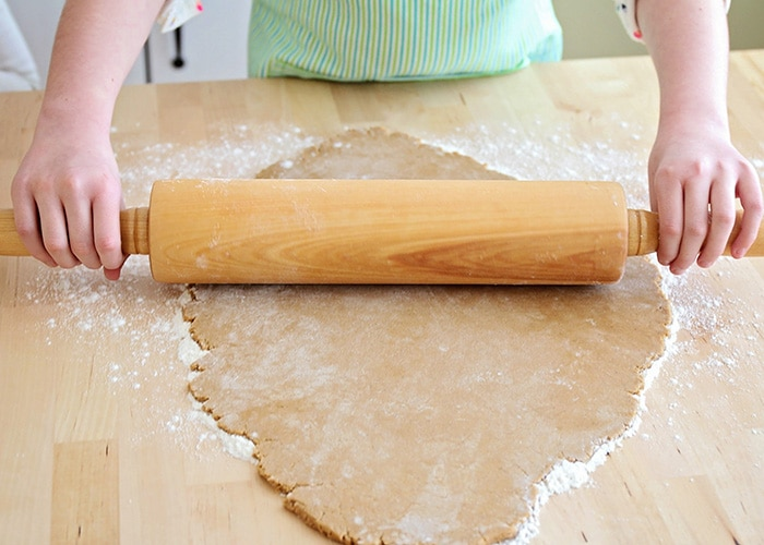kids hands rolling out gingerbread dough