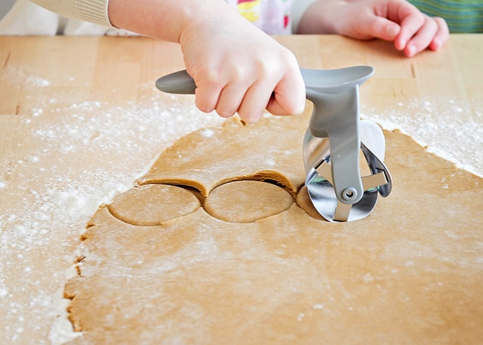 a rolling cookie cutter cutting out dough