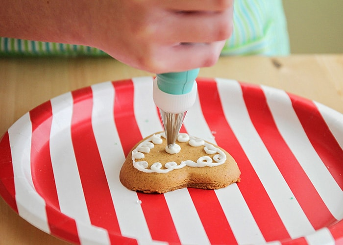 icing being piped onto a cookie
