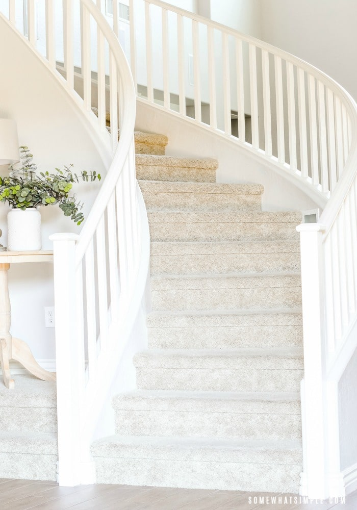 a winding staircase with a white wooden hand rail.