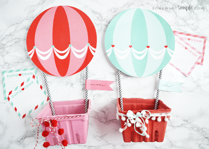 Two hot air balloon Valentine boxes. One is red and the other is a light blue.