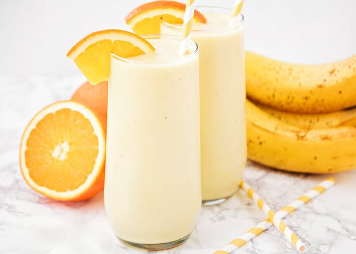 two glasses of this frozen orange creamsicle smoothie on a counter with oranges and bananas in the background and two striped orange straws on the counter next to the glasses