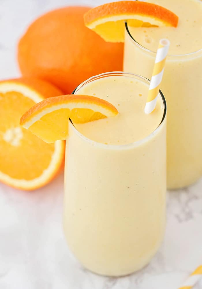 two glasses of frozen orange smoothies on a white counter