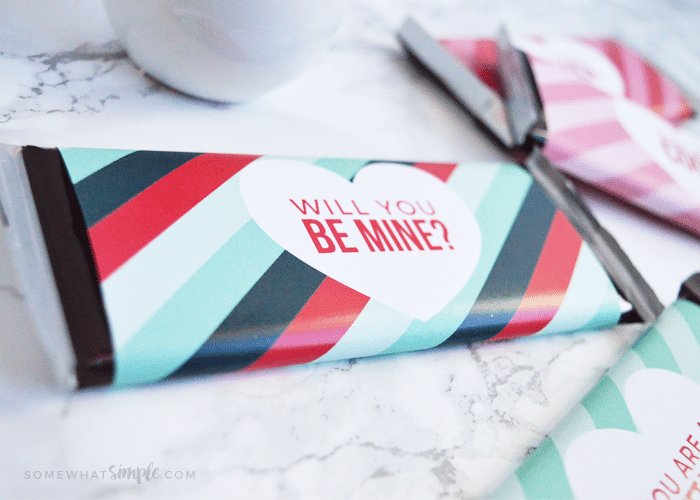 A Hershey candy bar wrapped in this Valentine candy bar wrapper printable that says Will you be mine?
