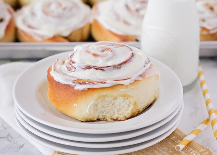 a homemade Cinnamon Roll topped with a cream cheese frosting on a stack of white plates with a jar of milk and a tray of cinnamon rolls in the background.