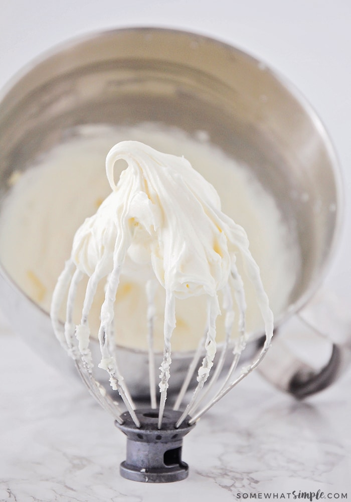 wire whip mixer attachment covered in this easy cream cheese frosting with a mixing bowl behind it filled with this homemade cream cheese frosting