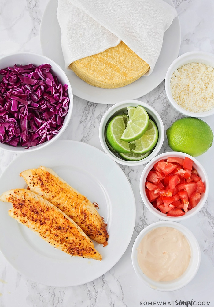 Looking down on the ingredients to make fish tacos; baked tilapia, purple cabbage, corn tortillas, lime slices, diced tomatoes, fish taco sauce and cheese