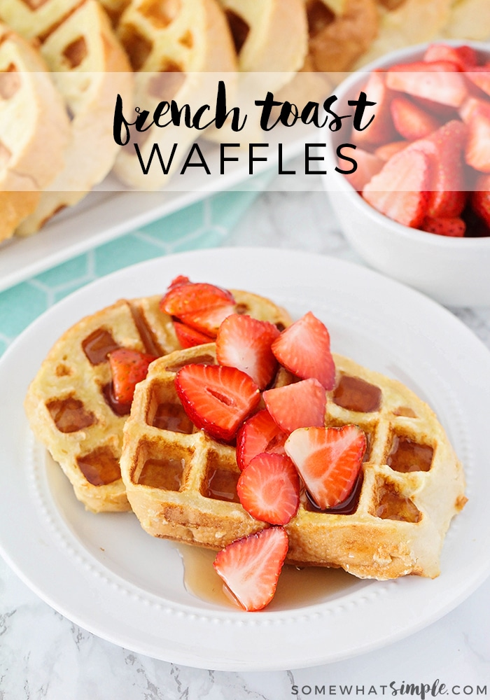 looking down on a plate of two French toast waffles made with this recipe that are topped with sliced strawberries and maple syrup. above them on the counter is a tray of more french toast made with a waffle maker and a bowl of sliced strawberries. The words french toast waffles are written at the top of the image in a translucent white box