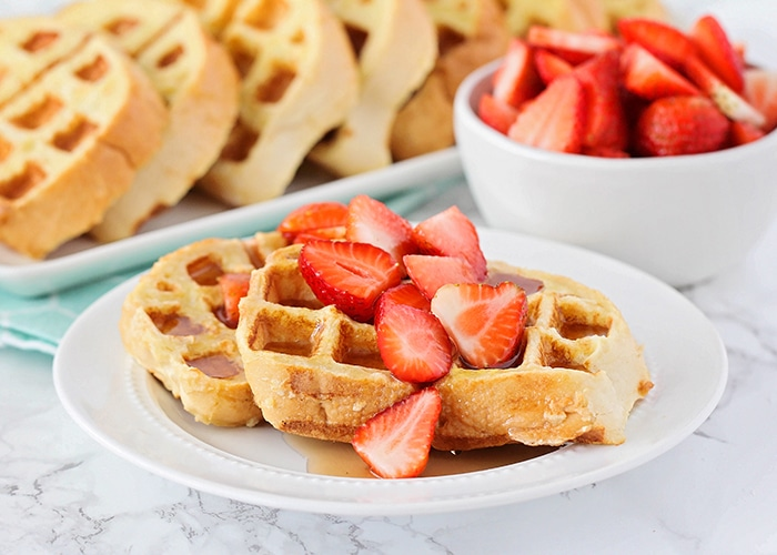 a white plate with two French toast waffles on it that are topped with maple syrup and sliced strawberries. A bowl of sliced strawberries and a tray of more french toast waffles are in the background.