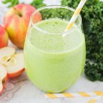a glass filled with a green smoothie and a yellow striped straw in the cup. Next to the glass on the counter are apples, leaves of kale and 2 more striped yellow straws.