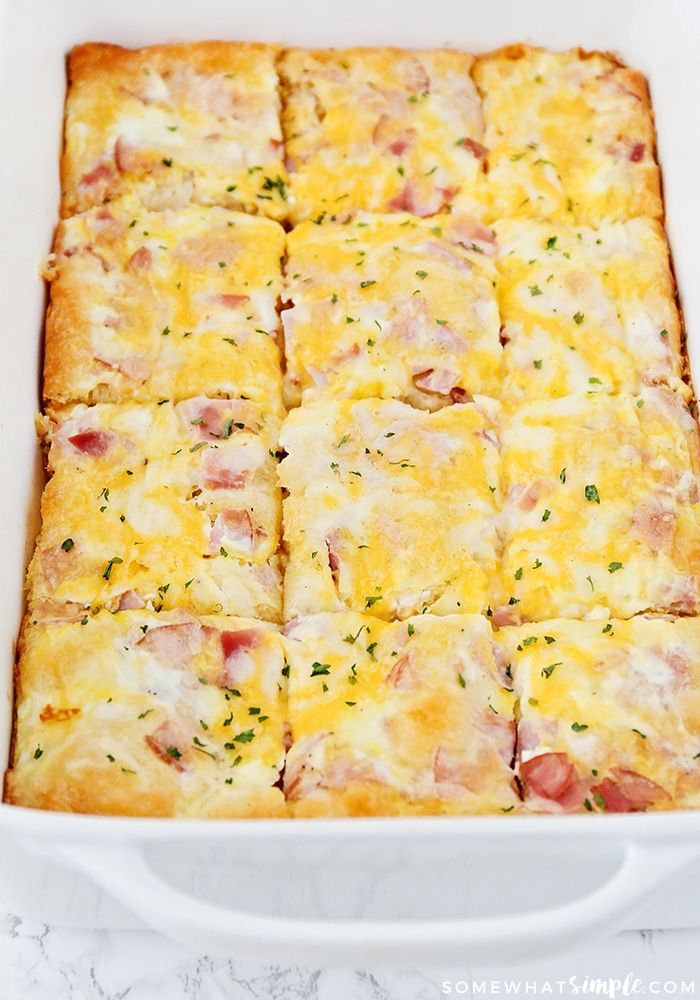 a casserole pan filled with a cooked breakfast casserole that was made with this easy recipe using cheese, eggs, ham and croissant dough and has been cut into twelfths.