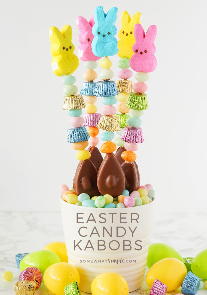a close up of five candy kabobs are standing up in a white bowl that is filled with pastel colored candies. The kabobs are made with various pieces of Easter candy. Plastic eggs are on the counter around the bowl. At the bottom of the image are written the words Easter candy kabobs.