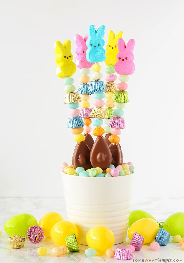 five candy kabobs are standing up in a white bowl that is filled with pastel colored candies. The kabobs are made with various pieces of Easter candy. Plastic eggs are on the counter around the bowl.
