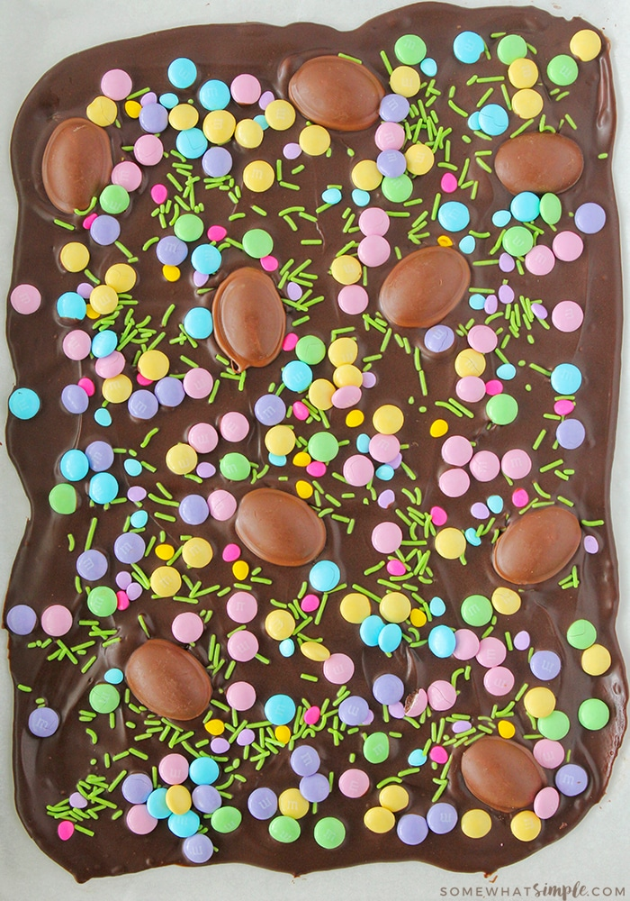 looking down on a cookie sheet filled with dark chocolate and pastel colored candy and chocolate eggs sprinkled over it