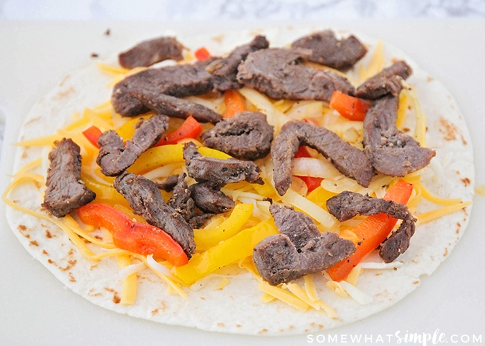 a tortilla topped with shredded cheese, steak, onions and bell peppers