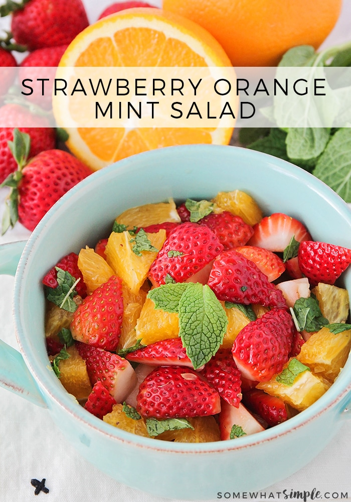a light blue bowl filled with sliced of strawberries and oranges and topped with chopped mint leaves. Behind the bowl whole strawberries, oranges and mint leaves are sitting on the counter. The words strawberry orange mint salad is written at the top of the image in a white translucent box.