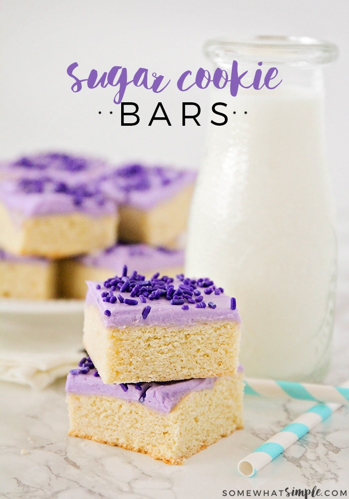 two sugar cookie bars are stacked on each other sitting on the counter top. The cookie bars are topped with purple frosting and purple sprinkles. On the counter behind the bars are two pastel blue and white striped straws, a pitcher of milk and a plate filled with sugar cookie bars made using this easy recipe. The words sugar cookie bars is written at the top of the image.