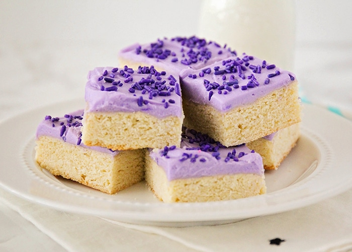 a white plate full of sugar cookie bars that are stacked on top of each other. Each cookie bar is topped with purple frosting and purple sprinkles. A glass of milk is on the counter behind the plate of sugar cookie bars.