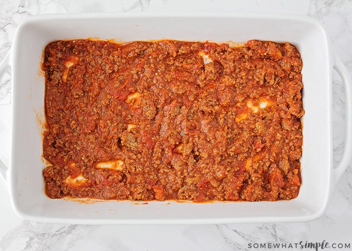 a casserole dish with a layer of homemade meat sauce on the bottom