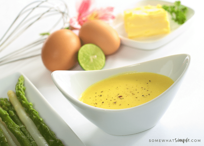 a white dish of Hollandaise Sauce made in a blender with this easy Recipe with a plate of asparagus next to it and eggs and butter in the background