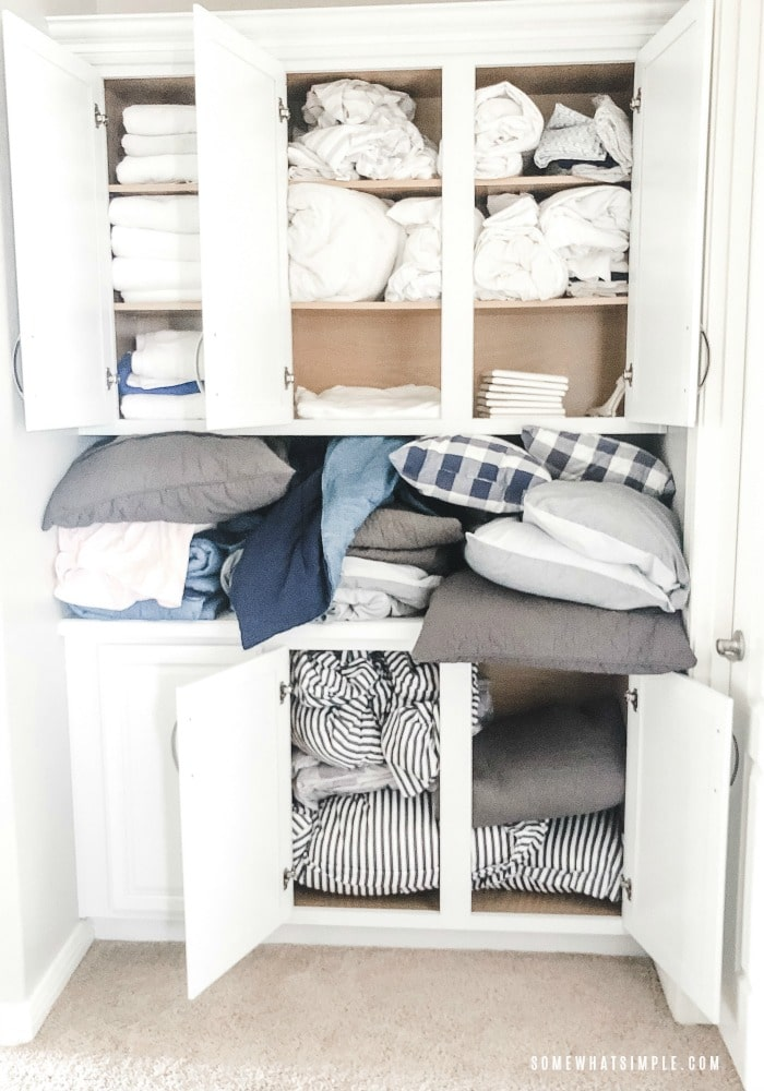 all of the doors of a linen closet are open revealing a mess of towels, pillows and sheets that are stuffed inside and completely unorganized.