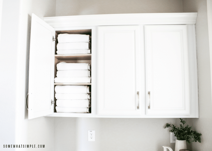 one door of a cupboard is open showing three levels of neatly folded white towels