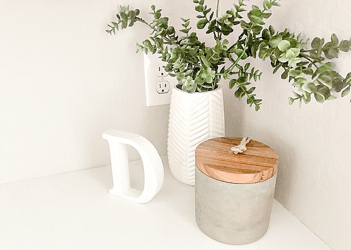 a plant, a wooden letter D and a decorative jar sitting on top of a white counter