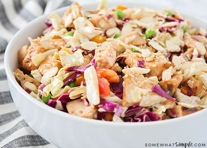 A close up of a white bowl filled with this easy Asian salad with chicken and vegetables