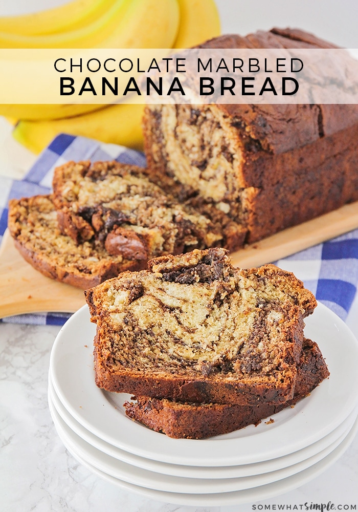 a loaf of chocolate banana bread in the background with a few slices cut off. Two of the slices are in the foreground on a small stack of white plates. A small bunch of bananas are in the background and the words chocolate marbled banana bread are overlayed at the top of the picture