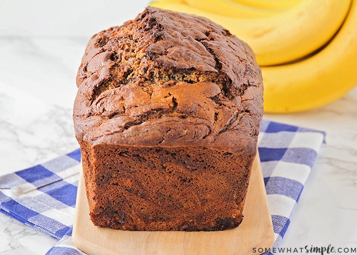 a baked loaf of chocolate banana bread on a counter made using this easy recipe with a bunch of bananas on the counter in the background