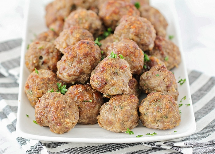 a white tray of homemade meatballs topped with parsley made using this easy recipe