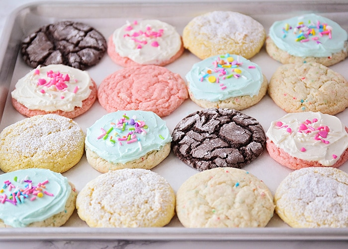 a tray full of easy cake mix cookies on a baking sheet. There are vanilla, strawberry and chocolate cookies on the baking sheet. Some of the cookies have white or blue frosting.