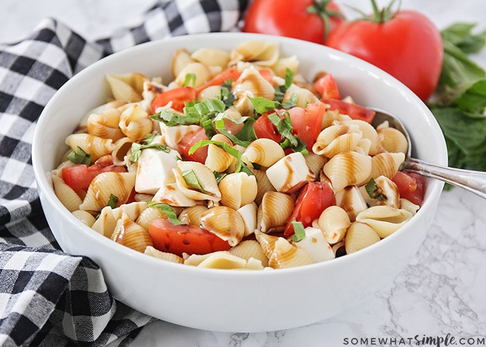 a white bowl filled with a caprese pasta salad that is made with shell pasta, fresh mozzarella, tomatoes and basil, tossed in italian dressing and topped with a balsamic glaze. A spoon has been set in the bowl and two tomatoes and fresh basil are in the background and a black and white checkered cloth napkin is on the counter next to the bowl.